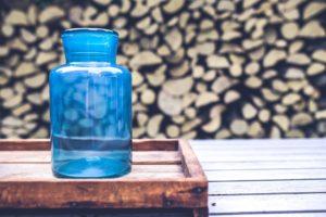 Blå glaskaraff på ett bord med vedträn i bakgrunden