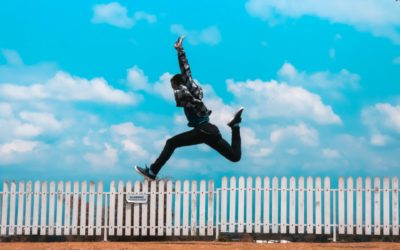 Kille som gör glädjehopp mot himlen i bakgrunden