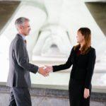 Handslag mellan man och kvinna i kostymer