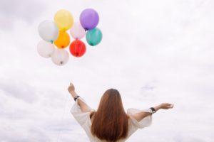 Kvinna står med ett knippe färgglada ballonger upp mot himmel, sett bakifrån.