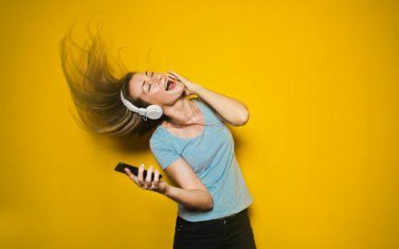Tjej med hörlurar och mobil i handen som dansar