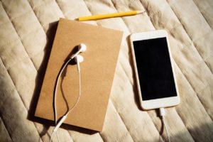 Mobiltelefon med hörlurar och block